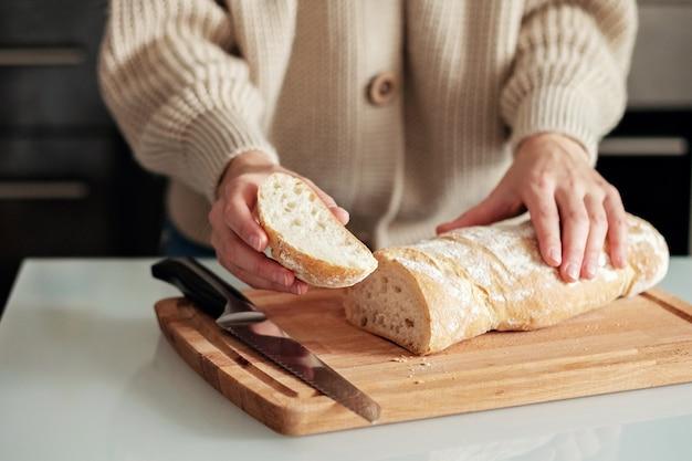 Primo piano di una donna che taglia il pane su un tagliere di legno