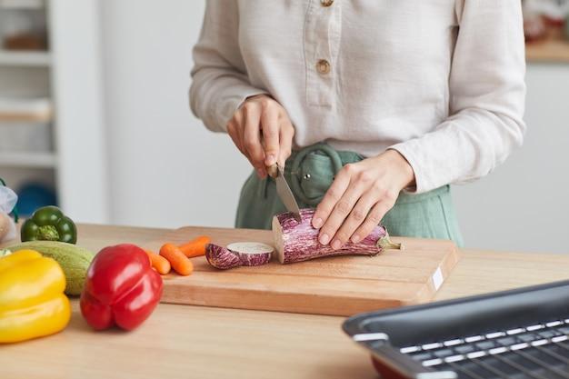 Primo piano della donna che taglia le verdure sul tagliere al tavolo della cucina a casa