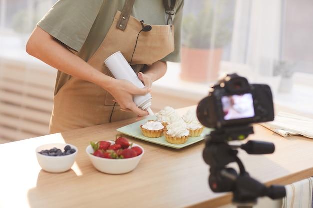 Primo piano di donna che decora torte al forno con crema e riprende il contenuto video in cucina
