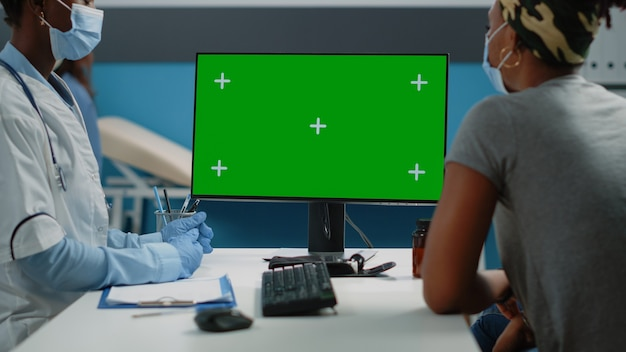 Primo piano di donna e dottore che guardano lo schermo verde sul computer