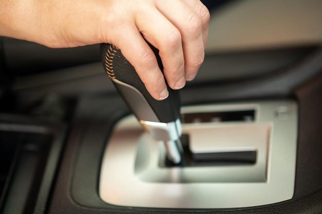 Chiuda in su del driver della donna che tiene la sua mano sul bastone del cambio automatico che guida come automobile.
