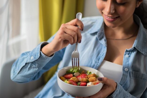 Primo piano di una donna che mangia un'insalata è seduta su un divano nella sua stanza