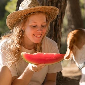 Donna del primo piano che mangia una fetta di anguria