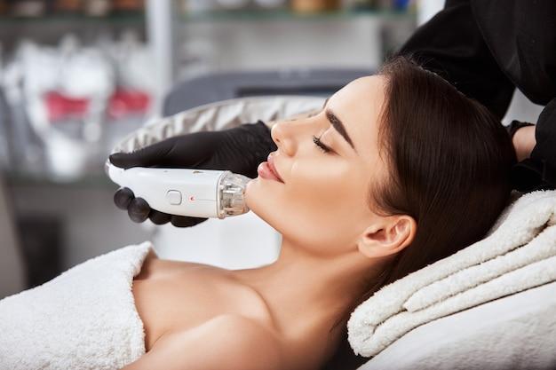 Primo piano del fronte della donna che ottiene procedura con il laser sul mento dal professionista nella clinica della stazione termale, viso perfetto della donna che ottiene il trattamento dal cosmetologo