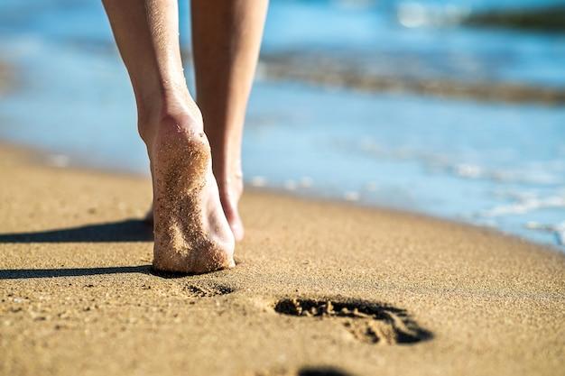 Chiuda in su dei piedi della donna che cammina a piedi nudi sulla sabbia lasciando impronte sulla spiaggia dorata. vacanze, viaggi e concetto di libertà. persone che si rilassano in estate.