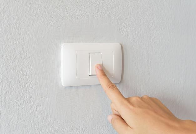 Chiuda su del dito della donna che accende l'interruttore della luce con lo spazio bianco della copia del fondo.