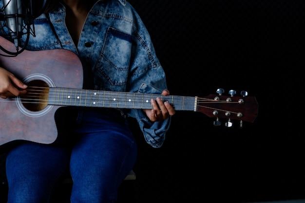 Chiuda sulle dita della donna che tengono il mediatore con una chitarra che registra una canzone nello studio di registrazione