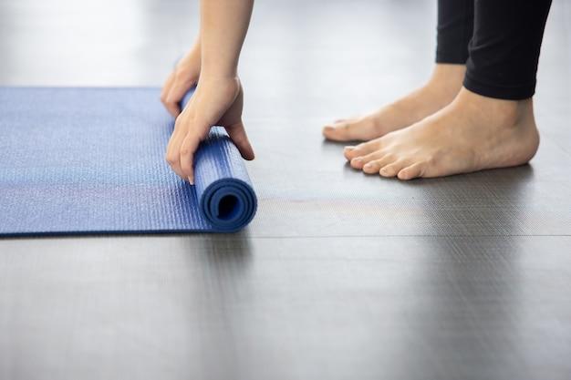 Primo piano sulla stuoia di yoga blu piegante della donna sul terreno dopo la lezione di yoha