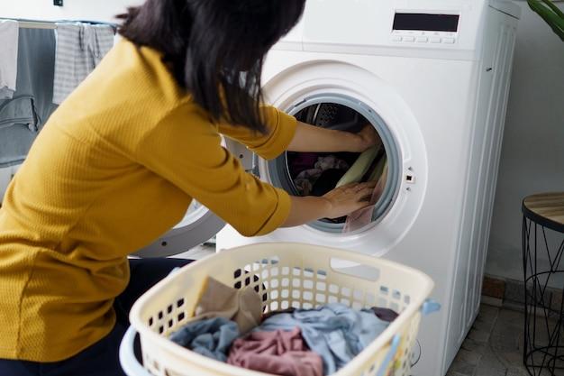 Chiuda in su della donna davanti alla lavatrice facendo un po 'di bucato caricando i vestiti all'interno