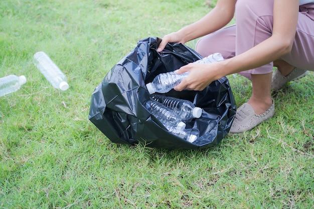 Primo piano donna la raccolta dei rifiuti è una bottiglia di plastica. concetto di conservazione ambientale earth day.