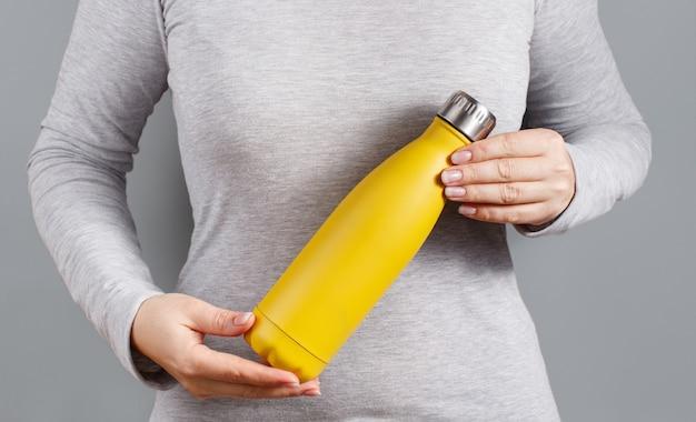 Primo piano di donna in tee grigio che tiene bottiglia isolata gialla su grigio