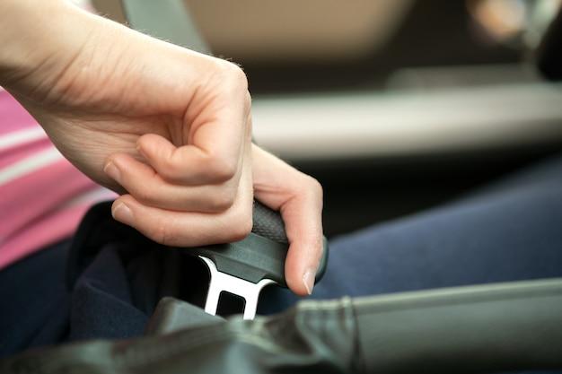 Chiuda su della cintura di sicurezza della legatura della mano della donna mentre si siedono dentro un'automobile per sicurezza prima della guida sulla strada