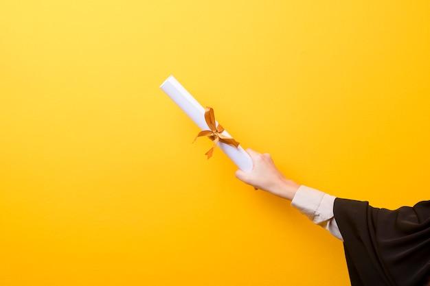 La fine della mano della donna in abito di graduazione sta tenendo il cappuccio e il certificato di graduazione su fondo giallo