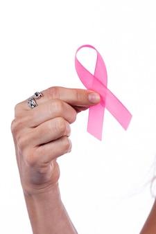 Chiuda in su della mano della donna che tiene il nastro del cancro al seno sopra un bianco.