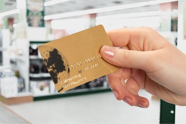 Primo piano della mano di una donna che tiene la carta di credito