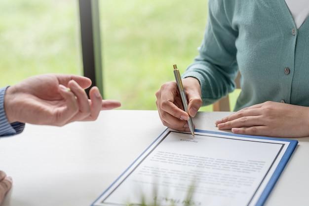 Primo piano di una mano di donna che tiene una penna che firma e un accordo di collaborazione in ufficio.