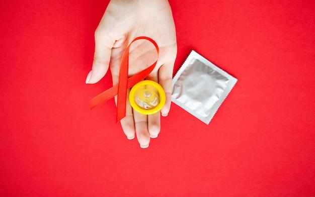 Chiuda sulla mano della donna che tiene il nastro rosso hiv, nastro di consapevolezza della giornata mondiale contro l'aids.