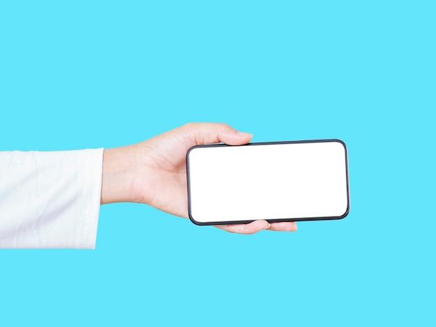 Primo piano della mano della donna che tiene smartphone con schermo vuoto, mock-up su sfondo blu