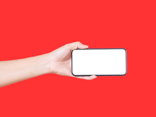 Primo piano della mano della donna che tiene smartphone con schermo vuoto, mock-up su sfondo rosso