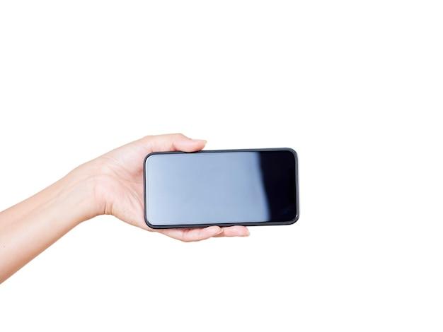 Primo piano della mano della donna che tiene smartphone con schermo vuoto, mock-up su sfondo bianco