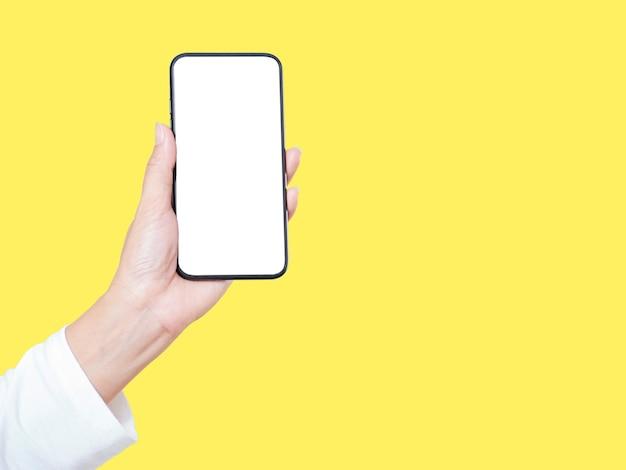 Primo piano della mano della donna che tiene smartphone con schermo vuoto, mock-up su sfondo giallo