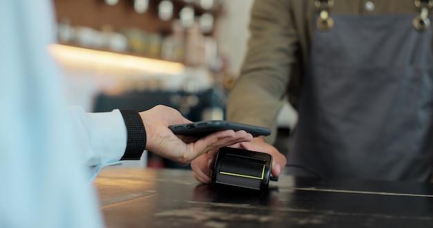 Primo piano di una donna che tiene in mano uno smartphone con una tecnologia di pagamento nfc utilizzata per pagare il caffè da asporto in un bar. il cliente utilizza il cellulare per pagare il caffè tramite un terminale per carta di credito.