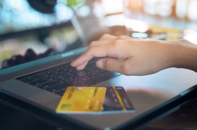 La mano della donna ravvicinata sta acquistando online tramite il computer portatile.
