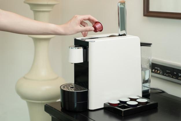 Chiuda in su della mano della donna premendo il pulsante su una capsula in una macchina per il caffè.