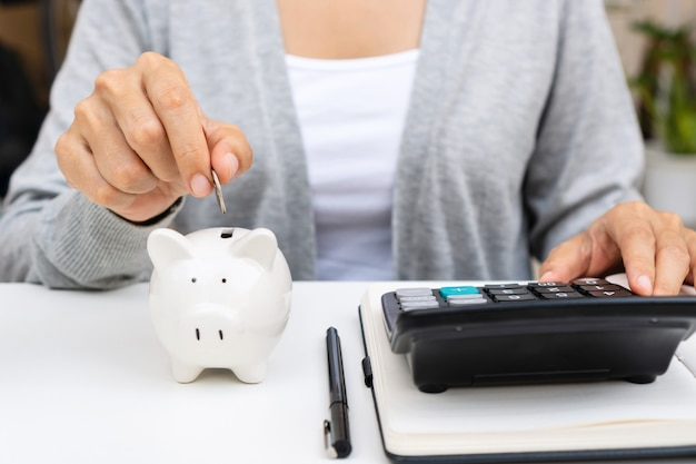 Chiuda in su della mano della donna che mette moneta nel salvadanaio mentre si utilizza la calcolatrice sulla scrivania bianca a casa. spesa familiare e concetto di risparmio.