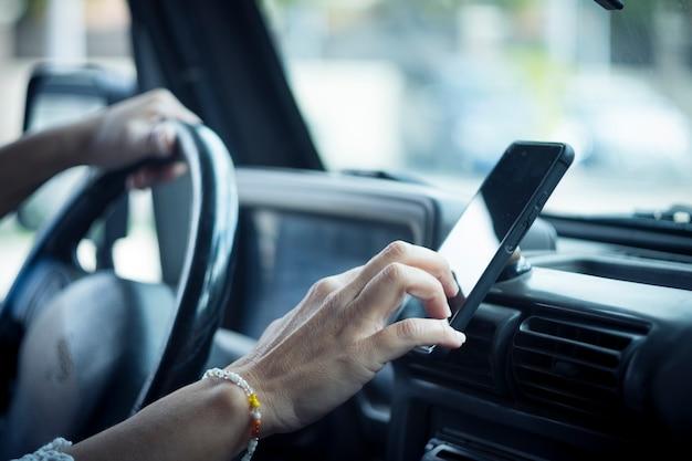 Primo piano della mano della donna che imposta il navigatore online gps sul telefono mentre guidi persone e viaggi con la tecnologia aiuta a trovare la strada utilizzando l'applicazione dell'app sul cellulare all'interno dell'auto