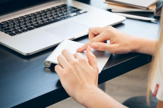Chiuda in su della mano della donna che tocca sul rilievo del mouse del computer portatile