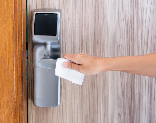Stretta di mano della donna utilizzando un panno umido antibatterico per disinfettare le maniglie delle porte della camera d'albergo.