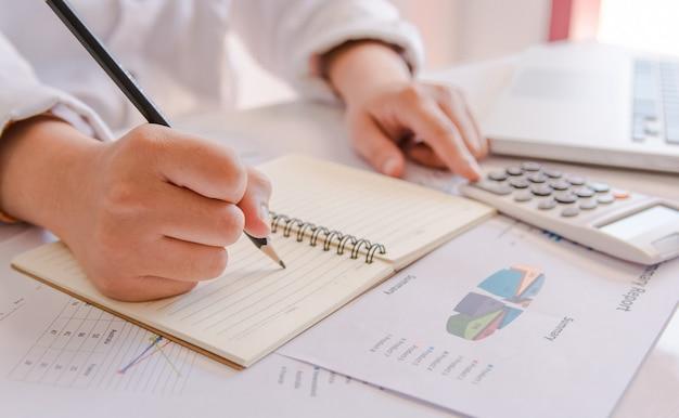 La fine sulla mano della donna facendo uso del calcolatore e la scrittura fanno la nota con calcola circa l'ufficio di costo a casa.