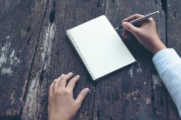 Chiuda sulla scrittura della mano della donna sul taccuino. scrittura della donna sul diario della carta per appunti sulla tavola di legno.