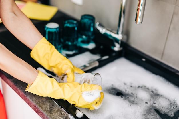 Primo piano della mano della donna in guanti di gomma protettivi gialli che lavano i piatti in cucina.