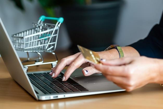 Primo piano delle mani di una donna che acquistano online con una carta di credito e un computer portatile, concetto di commercio elettronico