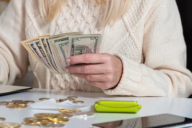 Chiuda in su delle mani di donna che contano soldi in dollari, personale finanziario femminile che conta denaro, finanza, risparmio e concetto bancario