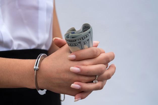 Primo piano delle mani della donna in manette che tengono dollaro. tangenti e corruzione