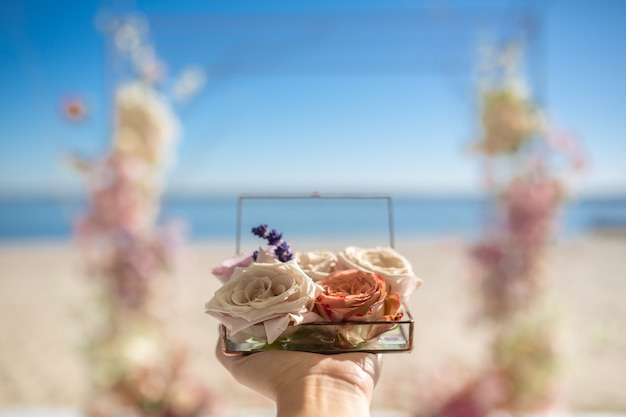 Chiuda sulle mani della donna tengono la scatola di vetro per le fedi nuziali decorate con i fiori di rosa freschi ed il mazzo di lavanda Foto Premium
