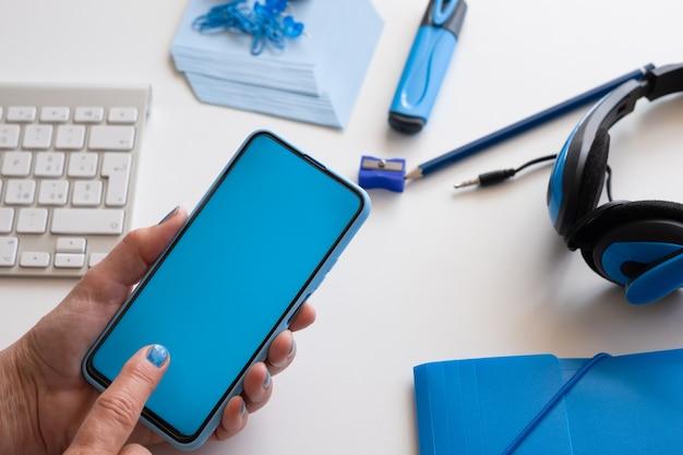 Primo piano sulle mani della donna che tengono lo smartphone con display blu. colore blu sugli accessori