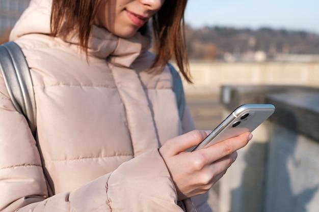 Chiuda sulle mani della donna che tengono una ragazza giovane dello smartphone utilizza il wi-fi o internet gratuiti di messenger