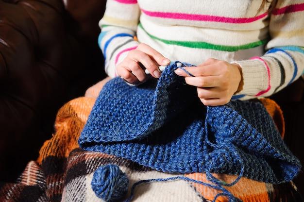 Primo piano delle mani della donna che tricottano il filato di lana variopinto