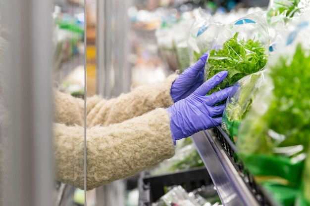 La fine delle mani della donna in guanti medici sceglie le foglie dell'insalata della lattuga aprendo il frigorifero in supermercato. protettivo contro il coronavirus
