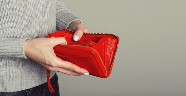 Chiuda in su delle mani della donna aprono un portafoglio vuoto.