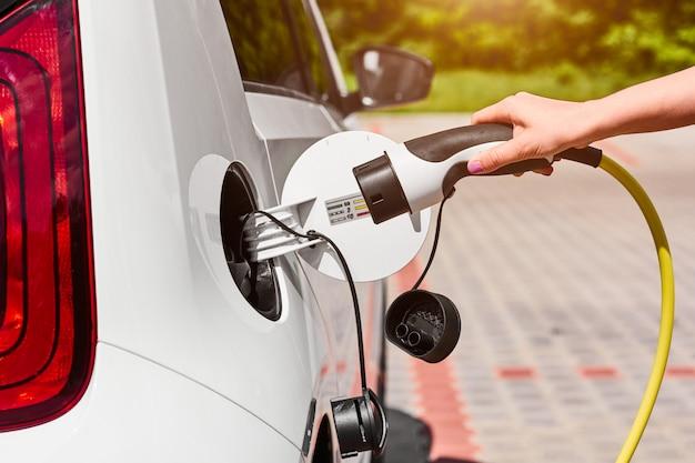 Chiuda sulle mani della donna che collegano un cavo dell'alimentazione elettrica all'automobile elettrica per caricare alla stazione di carico all'aperto.