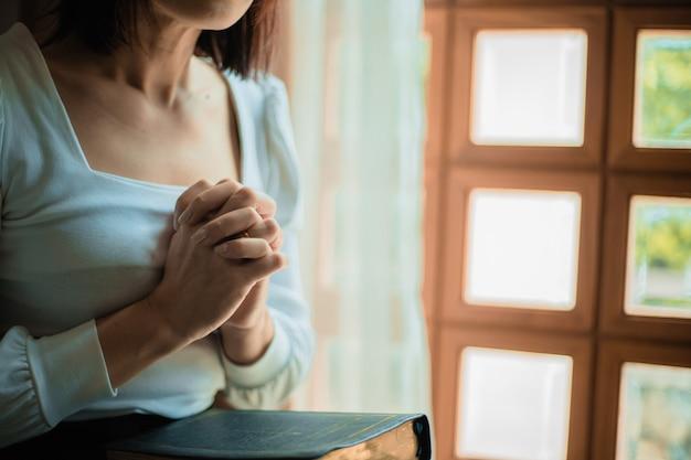 Chiuda in su delle mani della donna che pregano in chiesa, la donna crede e prega dio.