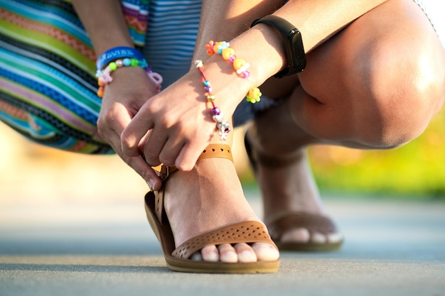 Chiuda in su delle mani di donna che legano le sue scarpe aperte sandali estivi sul marciapiede con tempo soleggiato.