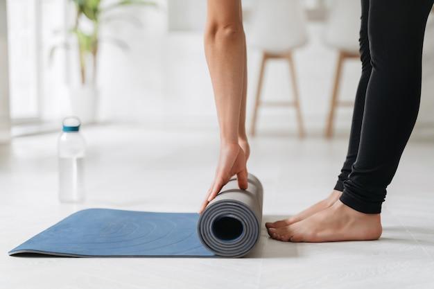 Chiuda sulle mani della donna che srotolano la stuoia preparando per allenamento fitness o yoga a casa