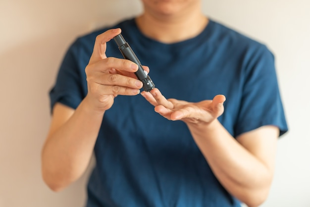 Chiuda in su delle mani della donna utilizzando la lancetta sul dito per controllare il livello di zucchero nel sangue dal misuratore di glucosio.