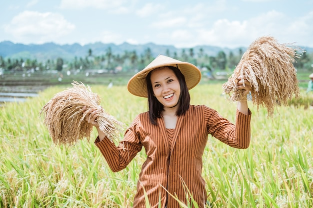 Primo piano di una donna in un cappello in piedi con le sue piante di riso nei suoi campi di riso dopo la raccolta
